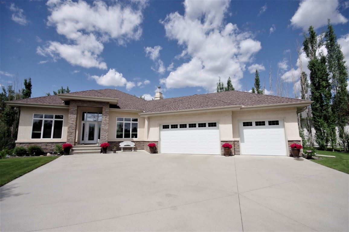 Gorgeous custom built home with over 3500 sq ft of developed space. This home backs onto the environmental reserve & Big Lake. Beautiful walking & bike trails lead to the Lois Hole Provincial Park. Open design living room with a gas fireplace, large kitchen with granite counters, island, walk-in pantry & breakfast nook. A formal dining room or flex room, den, large laundry room & direct access to the triple, heated garage with hot/cold taps & floor drain. The master bedroom suite has a garden door to the deck, a large walk-in closet & five piece ensuite with a jetted tub. Beautiful hardwood floors are on the main floor. The lower walkout level leads to a covered patio. It has been developed to a large family room with a gas fireplace & built-in wall unit, two bedrooms, a full bathroom, recreation area, hobby room & utility area. A garden door leads from the nook to the deck with a BBQ gas hookup & overlooks the fenced yard which is surrounded with trees giving you a private setting. On city water & sewer.