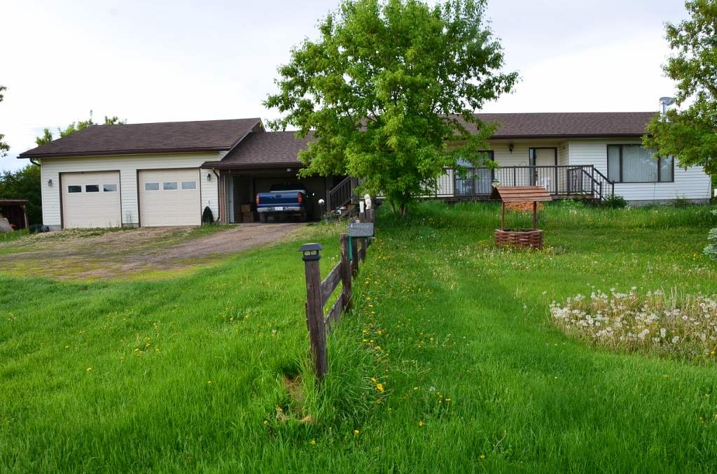 ATTRACTIVE/CLEAN/COMFORTABLE/MODERN ACREAGE.  2.98 acres with services, landscaping, 1355 sq ft bungalow, attached 16'x18' Mom's garage, covered carport, and Dad's double garage 26'x39'. This property is great for family or retirement.  Close to town and pavement. Nice yard and or Garden area. Buildings are good. Lots of room in house and garage/hobby shop buildings. Retiring senior's property. this is a winner.