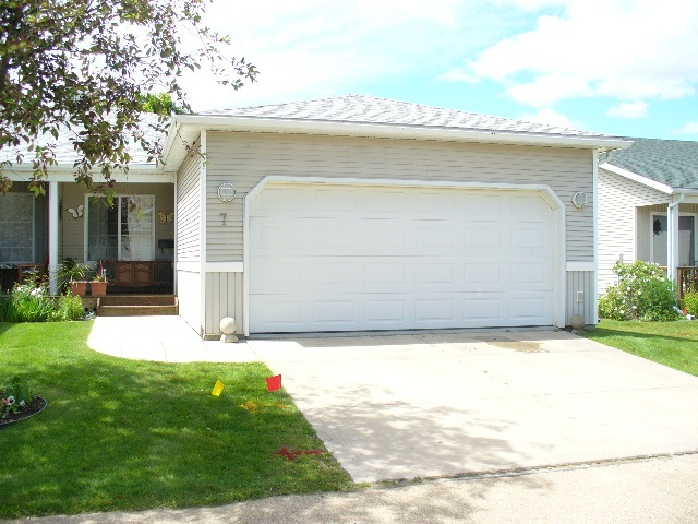 ENJOYMENT at the lake comes in the form of a 45+ condo. #7 has so many great features. Double attached heated garage (w/radiant heater), hot/cold water taps and great built-in shelving. This bungalow offers over 1200sq ft, main floor laundry. The first Bedroom/Den will greet you as you enter the unit. 4Piece main bathroom also has your laundry space. Open kitchen with blonde oak cabinetry, eat-in kitchen and great storage. Master bedroom has HUGE walk-in closet and 2nd closet for extra belongings and 4 piece ensuite. Living room offers you options with your furniture. Possibly a formal dining room, or enjoy the gas fireplace. Garden patio doors lead to a sanctuary of privacy, room for BBQ and current gazebo with tin roof for your entertaining pleasures. Enjoy the birds, the peace and the magnificent green space behind and beyond your unit. Basement fully finished with large 3rd bedroom, entertaining recreation room, plumbed bar and 3 piece bathroom. Shingles new 3yrs ago. Steps away from Village AMENITIES