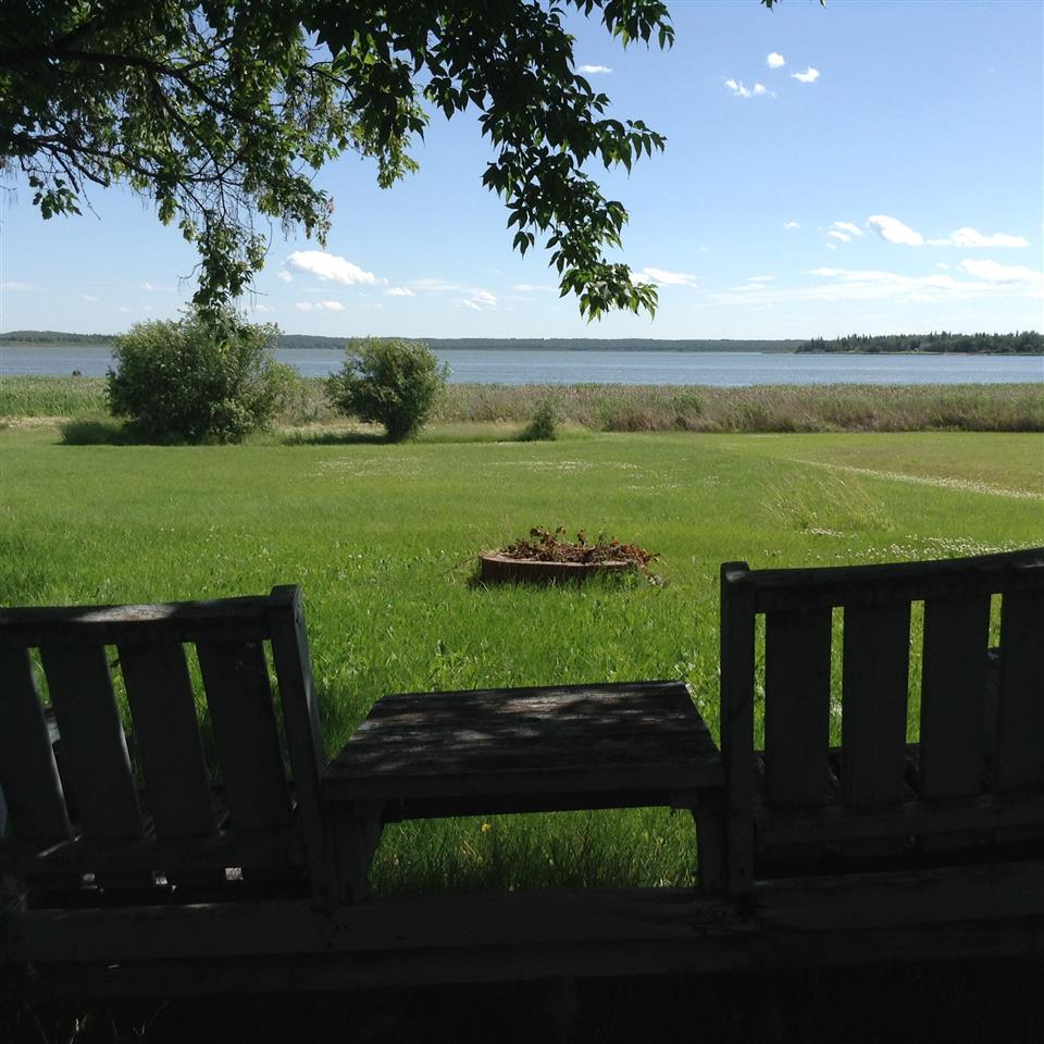 """Beautiful south facing WATERFRONT lot, only 35 paved kms from Edmonton's city limits. Tranquil setting and peaceful lake views! Relax in this friendly community, overlooking the calm waters of Sandy Beach and immerse yourself in Mother Nature's beauty. This 40' x 197' waterfront lot comes complete with a 1986 tandem axle, 36' fifth wheel travel trailer, sold """"as is, where is"""", and a 26' x 8' covered deck with galvanized steel roof plus a 12' open deck area protected from the elements by solar grey suntuf roof panels. You'll also find a 12' x 8' storage shed/outhouse with 20' overhang and 500 gallon holding tank. The lot offers both, a mixture of mature trees along with 11 young planted blue spruce. ...Refreshing ... Rejuvenating ... Relaxing ... Retreat."""