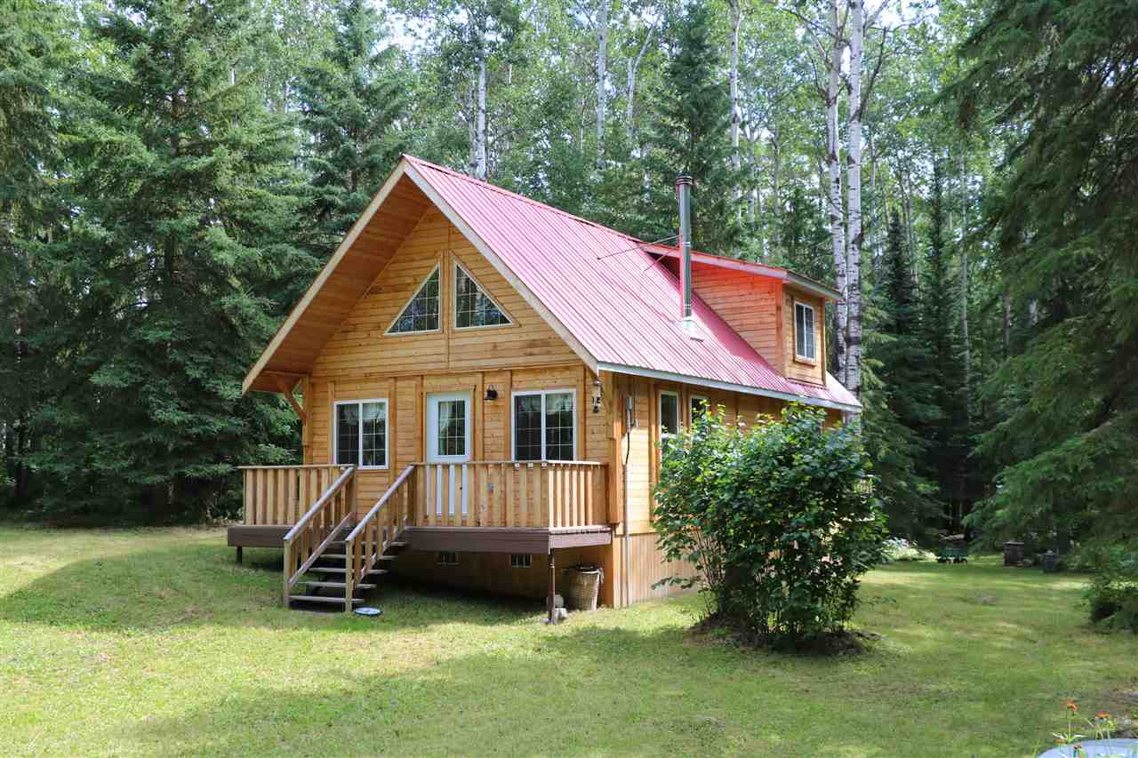 CABIN IN THE WOODS!! On a short PAVED commute just NW of the city you will find this completely private 6 acre oasis. As you wind down the treed driveway you will be greeted by the amazing knotty pine cottage with red metal roof. It is a wide open bungalow with loft cottage and features a woodstove and natural gas heat. The master bedroom is the loft area overlooking the main floor but one could easily add some partitions to make more bedrooms.  There is a bathroom with claw tub, a sink, and a composting toilet. No running water or septic tank so just bring some jugs along. This gem comes totally outfitted with furniture/dishes/etc. There are numerous other outbuildings such as sheds, an outhouse, and even an older cabin and reading cottage that could be easily used as a bunky for guests, or a getaway within a getaway! Fantastic stone firepit area that like the rest of the property is adorned with massive trees. There is 100 amp power and natural gas, so just add water and sewer to be fully serviced.