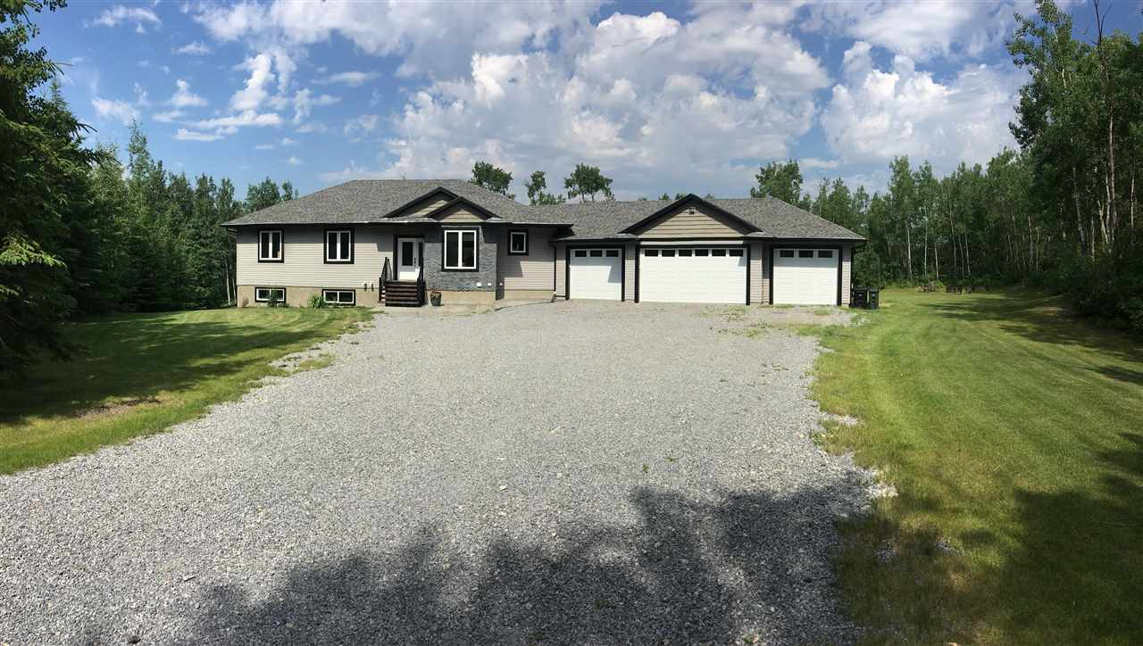 This custom walkout bungalow on 4 acres of land has 3600 sqft of living space and is a private paradise in the woods. Top of the line features include hand-scraped hardwood and tile. An open concept main floor with oversized windows for an abundance of light, a living area with floor to ceiling stone gas fireplace, and a large formal dining room, also 2 large bedrooms a full bath, ½ bath, & laundry.  The large master retreat includes a walk-in closet & ensuite with a custom stone shower. The fully finished walkout basement holds 2 additional bedrooms, a sound-proof room, a full bath with custom stone shower, wet bar, pool table,  120? projection screen, a cold room, all with the comfort of in-floor heating. Walk outside and enjoy the privately landscaped yard with the large partially covered duradek, fire pit areas, and pond. City water and high-end waste management system makes acreage living easy. The attached 24x62 four-car garage with heated slab, epoxied floor is the garage of your dreams.