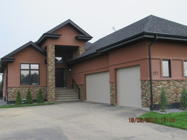 I don't know where to begin.. maybe the perfect location only minutes from Edmonton with municipal water or the Stunning floor plan offering 5 bedrooms, gourmet kitchen with 11 ft Granite Island with storage on both sides, soft close cabinets and amazing appliances.  It looks onto the great room with 13' Coffered ceilings, custom cabinetry and fireplace.  The Dining area gives you room for a huge table and it opens to a partially covered maintenance free deck. Master bedroom has 2 closets, double vanity, soaker tub and heated floors!!! Main floor has hard wood throughout.. Downstairs you will find a family room with a double sided fireplace with custom wall unit and separate exercises room overlooking the Rec area with huge wet bar and glass wine room. 2 more bedrooms with a full jack/jill bathroom     In floor heat, Fire suppression, Hot water on demand central air, triple pain windows, upgraded insulation and triple heated garage. Custom blinds throughout and upgraded lighting. Beautifully landscaped!!