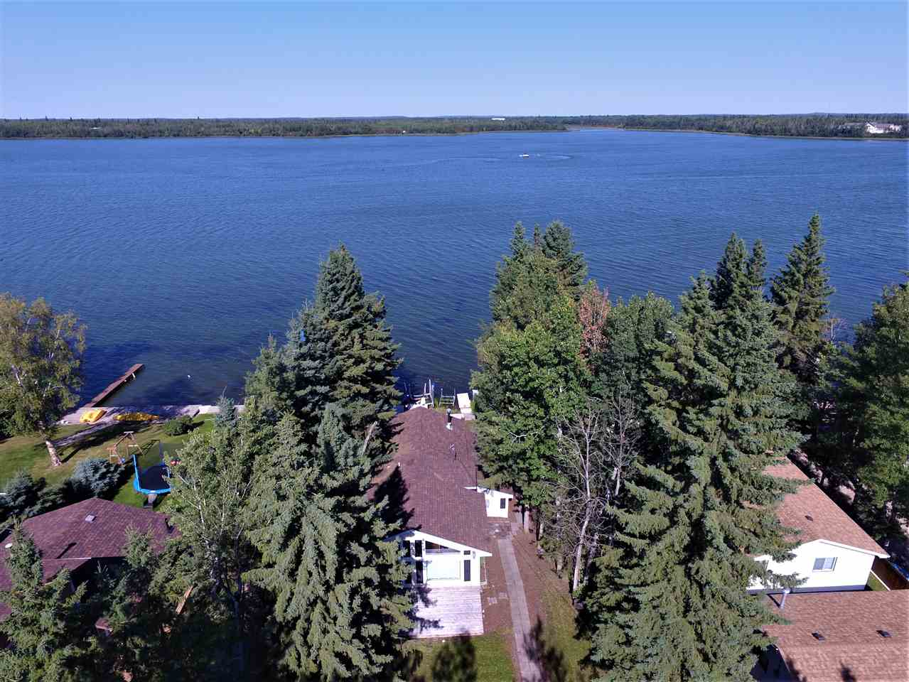 You will Love This Waterfront Property Located in the Summer Village of  Nakamun with 55 ft of Shoreline!! The Large Welcoming Foyer Features Slate Flooring with Plenty of Room to hang your outside gear. Just off the foyer is a Beautiful 4 PC Bath with a Claw foot Tub/Shower. The Laundry Room & Cabinets share the Bathroom Space. There are 2 Great Sized Bedrooms that each accommodate Bunk beds plus a Double bed. Large  Windows on the Front of the Cabin Brighten both Bedrooms. To the Right of the Cabin through the Gorgeous Glass Door is a Spectacular Open Concept  Kitchen/Dining and Living Area.This Home is Beautifully Designed with Open Beams and Vaulted Ceilings. The White Wainscotting throughout brings out the Character of Beach Living. You will Enjoy Cooking with High End Appliances and Prepping for the BBQ on the Large Island. Waterfront Views are Breathtaking from Large Living Room Window and even More Enjoyable on the Back Deck. Wake up in your Spacious Master Bedroom with the same Amazing Views!