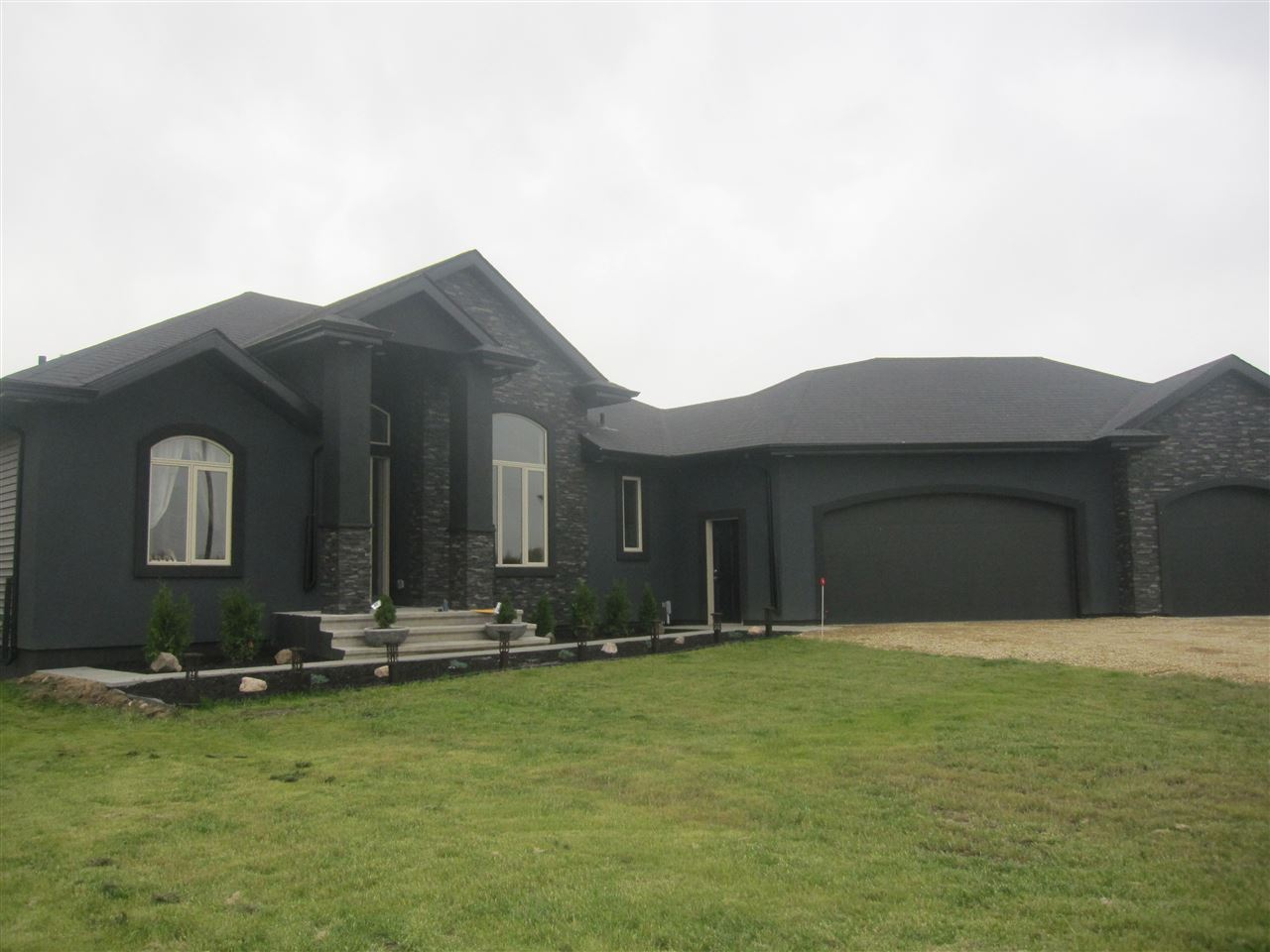 Absolutely gorgeous custom-built 1721 sq.ft. bungalow situated on 5 acres in Sanctuary Estates. approx. 30 minutes south east. Open plan with high ceilings in the great room and formal  dining area. Nice kitchen with a generous nook with access to a large south-facing deck. Spacious great room is hilited with an attractive floor to ceiling stone fireplace. Good size master has a walk-in closet and an elegant ensuite with jet-tub and separate double shower. Fully  finished basement has the 4th and 5th bedrooms, a huge rec room, wet-bar,  4 pce. bath and a THEATRE ROOM ( projector will stay). Fully finished heated triple attached garage.  Soft neutral colors throughout and tasteful use of maple hardwood, ceramic and quartz. Landscaping is complete. Truly a fine home for a family to enjoy!