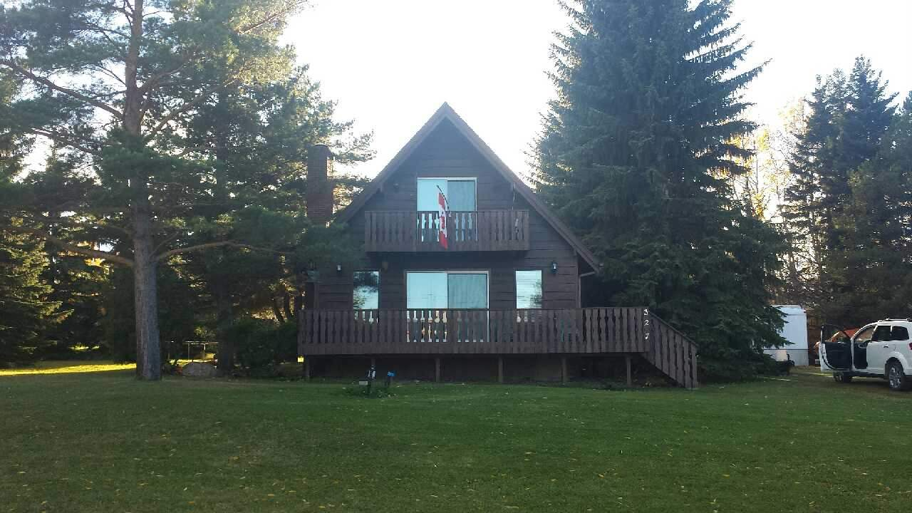 """Very nice cabin charm with cedar throughout in this 1007 sq. ft. 2 bedroom year round A-Frame home. Located on a """"no-through"""" road which has a day park at the end on the waters edge. Attractive wood burning forced air fireplace with Tindall stone facing, is sure to warm you up on those brisk days. There is a very peaceful rear yard to enjoy by the fire. There is a wrap around deck from the front down one side to the rear yard, very convenient, rear deck has natural gas BBQ hook up. Water access allows for a shared space on the water for the toys or to just enjoy the warm waters of Pigeon Lake, or the ski-doing and ice fishing in the winter. At the other end of the road is a play ground for the little ones. Don't miss out. There is a triangle of 112 sq. ft. taken off the rear corner of the lot for road allowance. The bare lot next door is also available for $129,000 extra."""