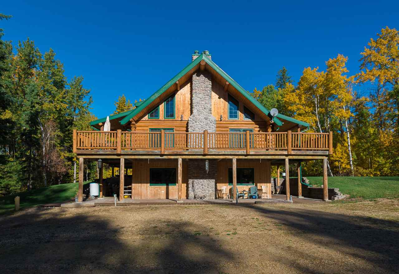 CUSTOM BUILT log home (2x6 walls on upper level & 2x12 ceiling) situated on 9.69 acres. This 2 Storey, 5-bedroom WALKOUT offers vaulted pine ceilings, Mountain Ash hardwood & tile throughout. Main floor features an open concept floor plan w/ plenty of NATURAL light. Large living area w/ stone gas lit wood burning fireplace. Kitchen has SS appliances, Jenair GAS STOVE cooktop, GE BUILT-IN appliances; dishwasher, oven, microwave & fridge with water line & built-in pantry.  Main floor has 2 spacious bedrooms w/ plenty of storage & 3pc bath w/ CLAWFOOT TUB. Upper level loft featuring the master bedroom and 4pc ensuite w/ jacuzzi tub and makeup counter. Walkout basement features IN-FLOOR heating throughout, large family room w/ pool table, wood burning stove & wet bar, 3pc bath and 4th & 5th bedroom. Electrical rough in for future hot tub. Additional features: central vac system, yard hydrant, walkout deck, fire pit area & pond (once stocked) horse pasture & space for future SHOP/GARAGE.