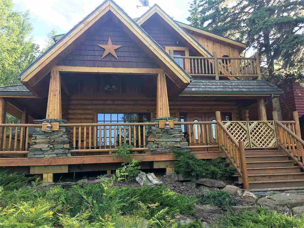 Great opportunity to own private retreat style home, 2 storey traditional log home has 3 bdrms with 1582 sqft. Main floor living design has stunning floor to ceiling w/b fireplace, well appointed kitchen with sit-up island, large open dining room, handy main floor laundry & 4pc bath. Half round log staircase takes you up to 3 bdrms, loft sitting area & 4pc bath. Elevated 60'x 120' lot has amazing views from large covered , wrap-around deck & upper balcony. ICF foundation and cedar shakes. In the back is a firepit & deck area + a 28'x24' garage, insulated, lined and has a small woodstove. Municipal reserve and towering spruce trees add privacy, close to playground, lake access & The Village. Quaint lakeside living at its best! For all waste water updates go to www.svofficepl.com