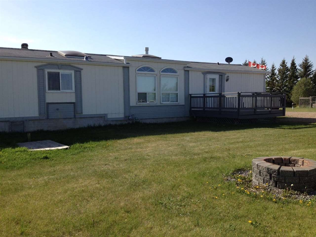 4.1 Acres situated in BrookWood Estates conveniently located 4 miles north of Vegreville on pavement. Featuring a 1996 mobile home with a warm and welcoming open floor plan of modern design; nice family home, very well maintained. Containing 3 bedrooms, 2 bathrooms, sunken living room with fireplace, addition with large office area and flex room, 2 decks and 3 skylights. Upgraded with new paint, window coverings, new carpet in the living room and master bedroom, water softener and R/O water system; plus, all appliances are included. Outbuildings include a double detached 28x30 heated garage/shop with a large concrete parking pad and an attached lean-to for additional storage and a 16x14 garden shed. Affordable family acreage with a nice backyard and firepit backing onto the open countryside and fenced for horses. GST may be applicable.