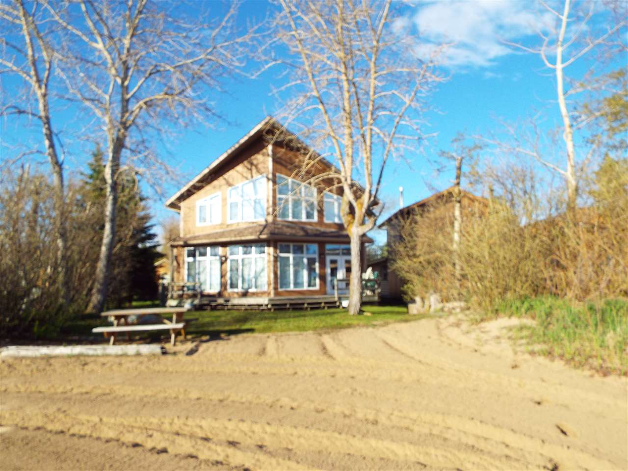 Sandy beaches and amazing sunsets! True LAKEFRONT at Pigeon Lake. Pavement all the way! Directly south of Thorsby on Hwy 778 to Sandholm Beach. Meticulously kept 6 bedroom year round chalet with all the amenities.  A lovely great room concept ideal for entertaining. 10 ft ceilings, gas fireplace, beautiful kitchen loaded with cabinets, separate family or TV room. Low maintenance linoleum in all high traffic areas. Carpeting throughout the upstairs. Total of 3 full bathrooms. Built on a 3 ft concrete crawl space in 2002. Large front and rear decks. Fully serviced with a drilled well, natural gas, electricity and MUNICIPAL sewer. A huge lot with room for a triple garage. Located on the north shore of Pigeon Lake, within 1 hour of Edmonton. BRING THE FAMILY, & BRING THE TOYS! LET THE GOOD TIMES ROLL!