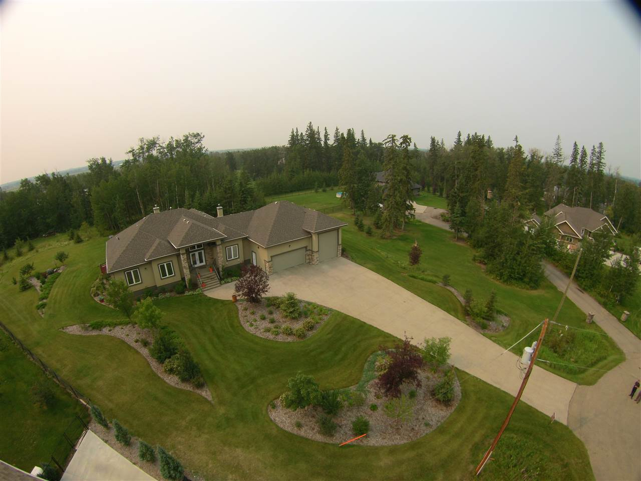 Executive acreage home w/ 2,579 sf., 5 bedroom bungalow on 1.07 manicured ares located on pavement, 5 minutes to Spruce Grove and 15 minutes to Edmonton. Impressive covered columned front entrance lead you to a grand entrance and spacious tiled foyer and den or possible bedroom. 13' ceiling in the great room w/airtight stone fireplace and south facing low-e windows. The kitchen is a cooks dream and offers cupboards/drawers galore, huge island/eating bar, granite counter tops, amazing walk through pantry, spacious eating area, w/ access to the 14x16 covered deck. Amazing master suite with 6 pce ensuite w/steam shower and huge W/I  closet. There's more, the spriral staircase leads to the huge basement w/rec room & 2nd fireplace, wet bar, exercise/theatre room, bedroom,  w/wiring for entire house audio system. Air conditioned, in floor heat. Professionally designed landscaping,  38x40 garage, room for 6 cars or RV. Aggregate driveway. Private door to basement. This is truly a defining address.