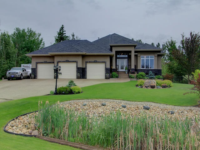 Executive walkout bungalow in prime location of Lake Ridge Estates just 10 paved mins w of Edmonton, 10 mins e of Spruce Grove and 30 mins to the airport! Backing green space and just steps away from Lois Hole Provincial park in a quiet culdesac lies this Elegant and Pristine home that encompasses just under 5000sqft of fully finished living space. Be captivated by the nature and natural light that the floor to ceiling windows exude as well as the water fall feature that displays in the massive foyer! The detail and quality is exhibited throughout this prestigious home with 9ft coffered ceilings, pot lighting, arched doorways, bay windows in master bedroom and family room,surround system, A/C. 2+3 bedrooms, 3.5 baths including half bath in the 40x28 heated garage. Office, formal dining room, breakfast nook, spacious kitchen with granite, recreational room, exercise & games room, media room. Walk out basement to an oasis including hot tub, fully fenced manicured yard encompassing trails and perennials.