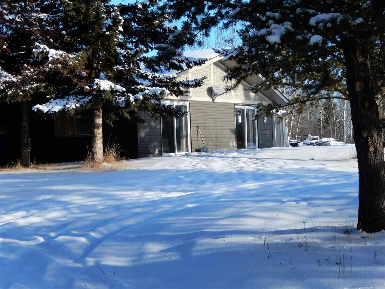 GREAT LOCATION! Singing Hills subdivision sits west of SEBA BEACH COMMUNITY. This quaint 1020 sq ft bungalow sits on a nice private lot with plenty of trees surrounding a large cleared area. The layout is quite open & has 2 bedrs & 1 bath. The year is estimated to be a 1982.  Most of the walls are done in PINE TONGUE & GROOVE to create a cozy feel. The floors are LAMINATE PLANKING/CERAMIC TILES. There is a 10x34 CONCRETE PATIO at the front of home. Property is partially fenced with CHAIN LINK on one side & other types of fencing on the other sides.