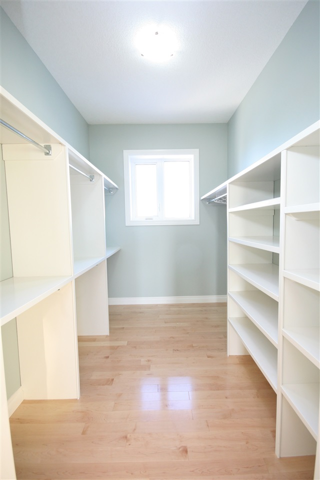 A pocket door slides open to reveal the sizable walk-in closet with built in organizers.