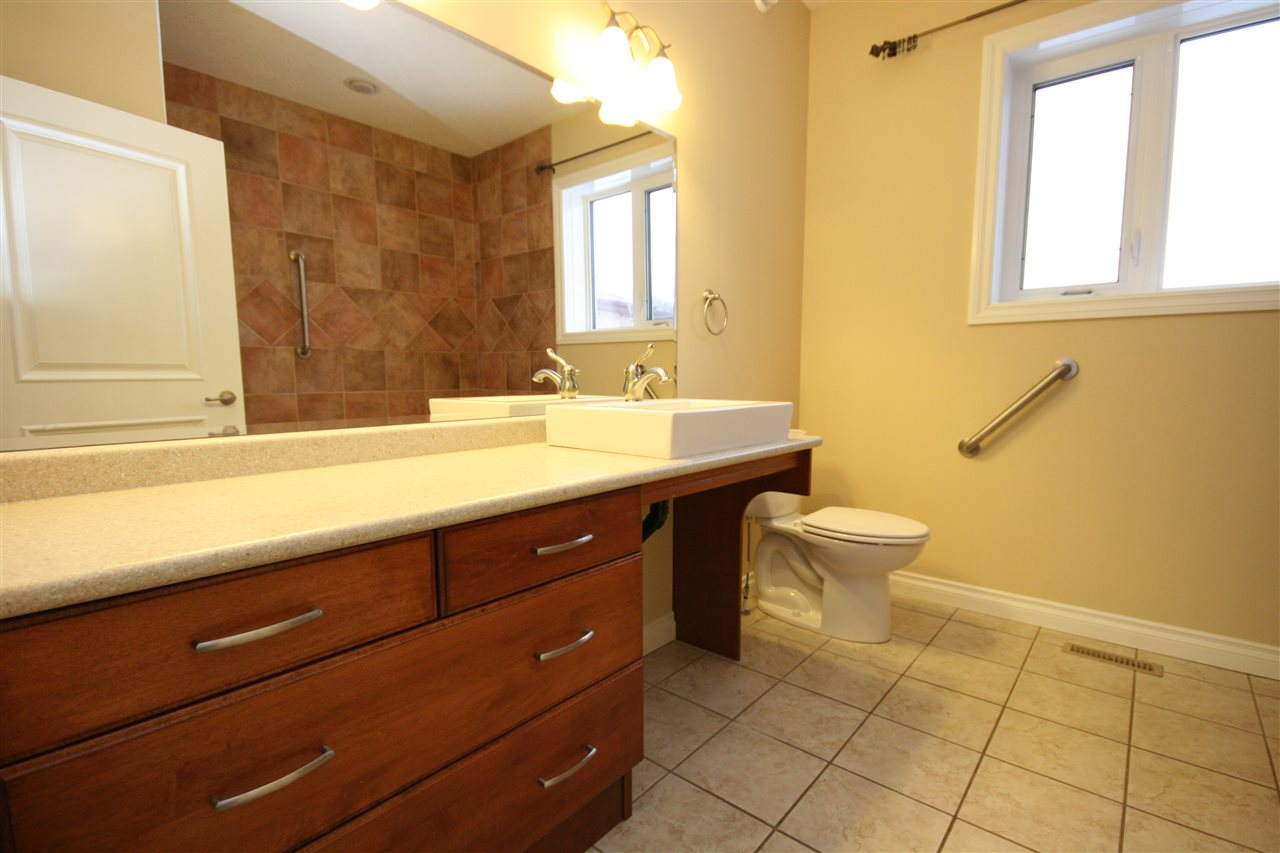 The master ensuite features an large vanity with deep storage drawers, extended mirror and tiled floors.