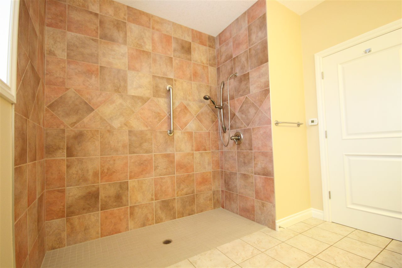Equipped with a barrier free, oversized shower that is tiled to the ceiling and has a heat lamp above.