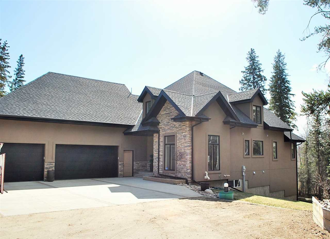 Imagine waking up every morning on a Jasper Park Lodge getaway! Peace, Serenity, Privacy and Cozy are just a few words to describe this beauty of a home. Located on 5.91 acres, OUT OF SUBDIVISION, FULLY FENCED w/ ELECTRIC GATE AND FULLY TREED, and only 8 MINUTES SOUTH OF SPRUCE GROVE. Walk in and you'll be blown away by the craftmanship of this custom built 1 1/2 storey. From the hardwood flooring, the huge windows & the breathtaking open concept design, this home has one of the most functional floorplans! The main floor features a 2pc. bathroom, den (5th bed)massive mudroom w/ Main floor laundry, a walk-through pantry to the GLORIOUS KITCHEN W/ GRANITE COUNTERTOPS, CERAMIC TILE FLOORING & STAINLESS APPLIANCES. The living room & dining area are also breathtaking w/ amazing views of the nature. The master on the main floor is every woman's dream and so is the 5PC. ENSUITE WITH HIS & HERS CLOSET. Upper level is 2 bdrms w/ a shared 5pc. ensuite & a bonus room. WALKOUT BSMT. with 4th bed, cheater 4pc. ensuite