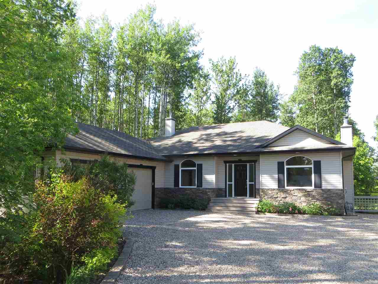 A park like setting on your own land! Private treed 3 acres with trails, and no neighbours behind you. Meticulously kept  home w/ open floorplan & vaulted ceilings has over 3500 sq ft of developed space. Double heated garage 24x22 and a 24x32 heated shop with attached shed + RV parking pad has room for all your toys. Tile and hardwood flooring, 9 foot ceilings, wood fireplace, maple kitchen with ample cabinet space including pot and pan drawers. The master bedroom can be your retreat with soaker tub ensuite. A den that could easily be a 2nd bedroom is on the main floor. Circular staircase leads you to the basement, a perfect hangout area w/ family room, media room, wet bar/kitchenette, 2 large bedrooms with walk in closets & a full bathroom. In floor heating to keep you warm, plus the 9 foot ceilings and large windows brighten the space. Enjoy the secluded setting off your maintenance free deck. All this 4 minutes from Spruce Grove!