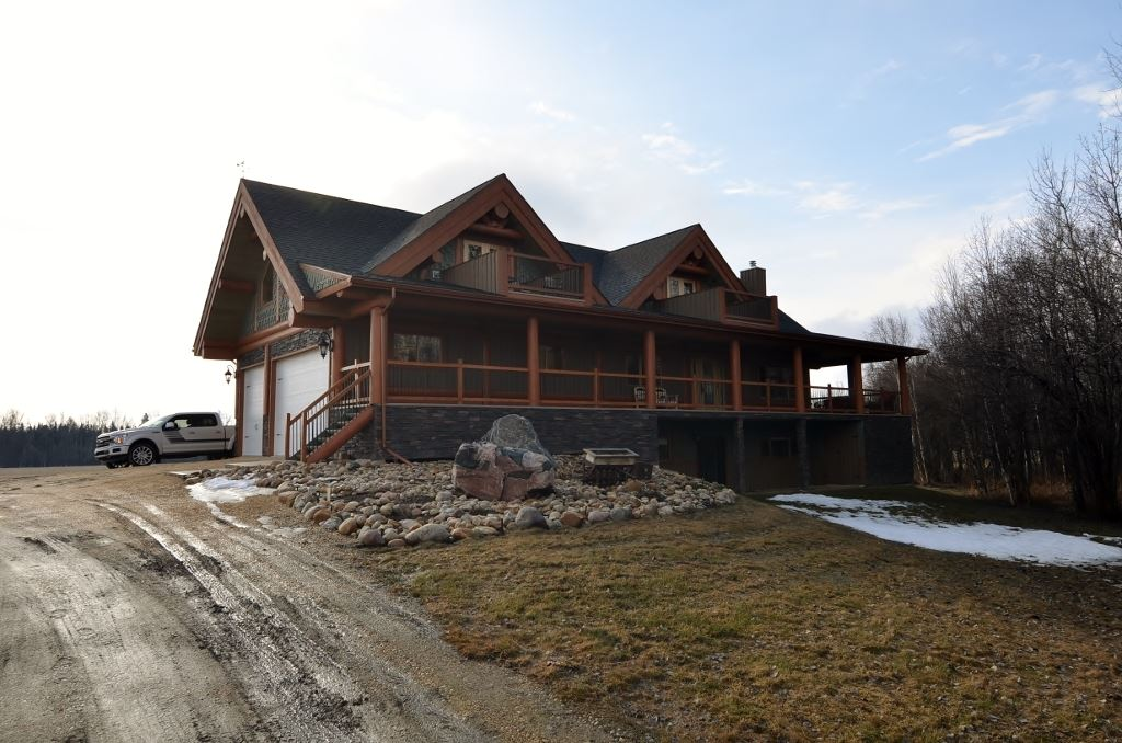 Absolutely Gorgeous Log Frame Home only miles from Town of Barrhead limits along hard top roads. This property was developed in 2014 w/ no expenses spared. 2400 sq ft of Dream home space. Main floor accents include floor to ceiling Rock faced fireplace, Open riser timber staircase, High vault ceiling, Granite counters, Interior log beaming, Dramatic wrap around covered sitting & entertainment deck plus more. Fully self contained single bedroom suite can be found above the garage w/ views overlooking the pond & yard. Walk out basement is fully finished w/ recreation room, 2 additional bedrooms, storage & utilities. Over-sized attached double Garage plus convenient high wall R.V Shop across the yard. Sheltering bush between Home and highway. Large & scenic central rock lined fish pond w/ round-about gravel driveway completes the focal point of the property. Words can't describe the details & feel. Must be seen in person. Ready & awaiting you.