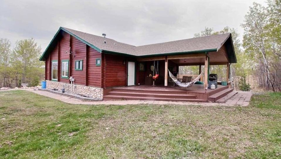 Beautiful views & privacy from this unique hillside acreage! Located right by Onoway & being only 20 min from St. Albert & Stony Plain, this property is ideal for outdoor lovers: bungalow style log home is located on top of the hill & surrounded by mature trees, fully fenced, with a massive deck & covered outdoor entertaining area at the back, hot tub, BBQ area, firepit area, plenty of sitting room! The home itself has a very homey feel with open concept entryway, living room with wood stove, dining area & kitchen! Large south facing windows make the home nice & bright. Custom kitchen has stainless steel appliances, huge pantry & is next to the mudroom with laundry & 3 pc bath. Two spacious bedrooms complete the upstairs (4 pc ensuite in the master!). WALKOUT BASEMENT is the entertainer's dream: large family room, handcrafted walnut & red maple bar, massive theatre room, 2 bedrooms & 4 pc bath, infloor heat! This property would not be complete without 60x40 finished heated shop with dog run & greenhouse!
