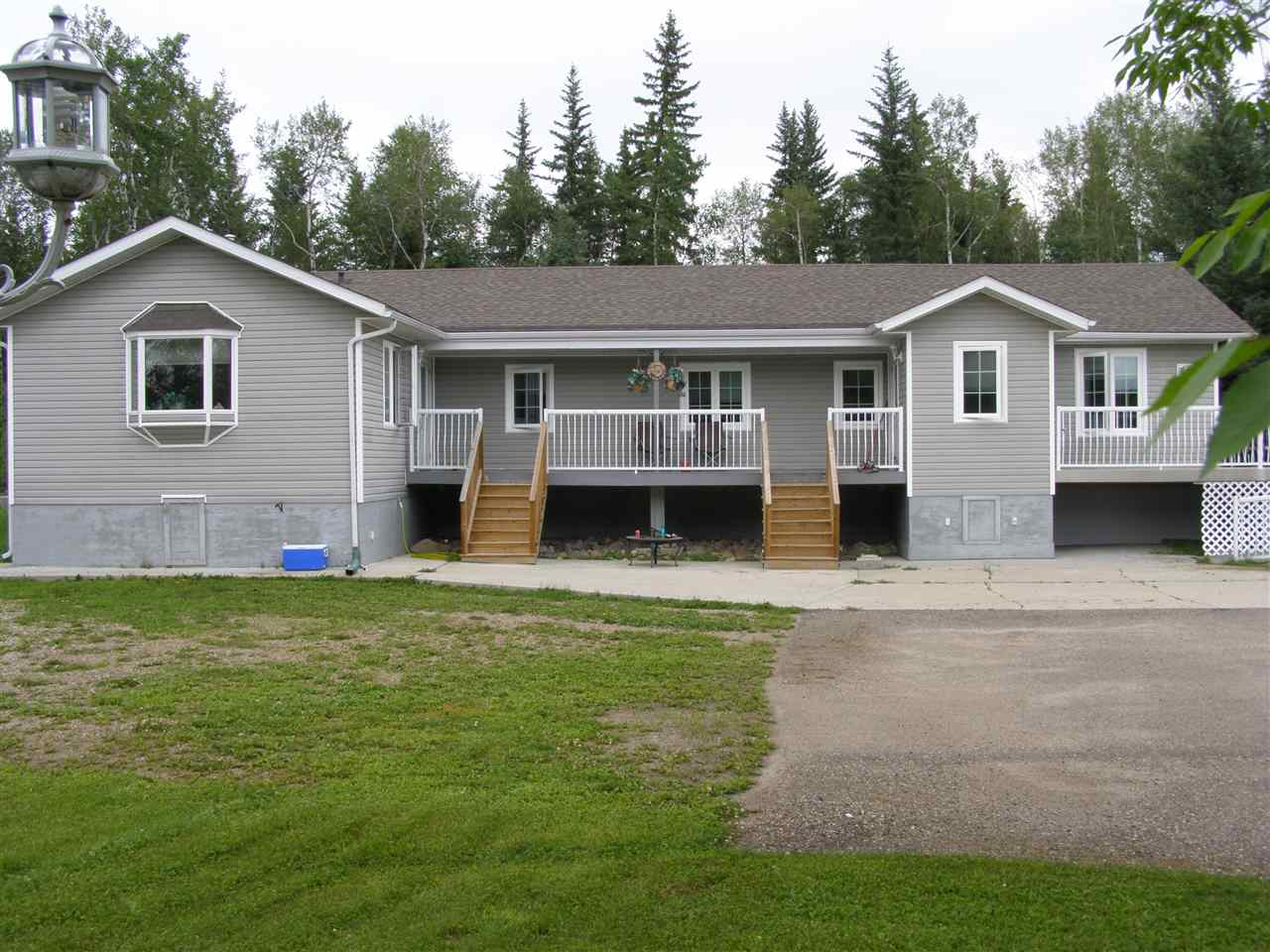 Tucked away on 4.97 very private acres sits this 2150 square foot home just 10 minutes west of Cold Lake off Hwy 55. Gorgeous kitchen has quartz countertops and stainless steel appliances. Large open concept living room/dining room has a handy propane stove with access to the huge deck and the beautiful setting outdoors. The palatial master bedroom has double doors to the ensuite with whirlpool tub and separate shower as well as access to the covered deck. Four additional bedrooms, a den (or kids playroom) and laundry area with quartz countertop/laundry sink complete the inside. Entire living space is on one floor, entrance has doors wide enough for a wheelchair and there is a ramp up to the side deck. The home has reverse osmosis water system and additions are on a heated concrete crawl space. Outside there are 2 large powered sheds (16x18 shed had hookups for heat and 20x24 shed has cabinets), fire pit area, beautiful trees and concrete parking area. Great location, priced right and picture perfect!