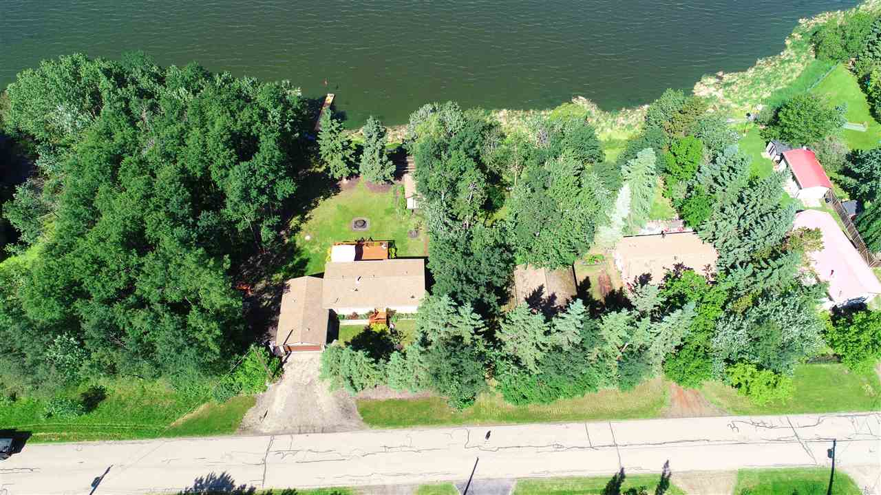 ABSOLUTELY SPECTACULAR LAKE FRONT RAISED BUNGALOW ON A VERY WELL LANDSCAPED LOT WITH A WONDERFUL PAMORAMIC VIEW OF THE LAKE AND SIDING ONTO A FORESTED RESERVE PARCEL. UPGRADES TO THE HOME INCLUDE SHINGLES, SIDING & STYRO INSULATION ON THE HOME, GARAGE & SHED, EAVES & SOFFITS, GARAGE DOOR, WINDOWS & DOORS, EXTENDED DRIVEWAY & CULVERT, BACK DECK & FRONT LANDING, 32' DOCK, SEPTIC PUMP, HIGH EFFICIENT FURNACE, SUMP PUMP, LIGHT FIXTURES, PAINT, APPLIANCES, STEEL FIREPIT, AND MORE. A VERY NICE FEATURE OF THE PROPERTY IS THE HIGH PRESSURE CITY WATER LINE FOR THE HOME AND ALSO A GROUND FED WATER WELL. THE OVERSIZED DOUBLE GARAGE HAS DOORS FRONT AND BACK. ALSO BOASTS A PROFESSIONALLY DEVELOPED BASEMENT. GREAT ACCESS TO ELK ISLAND PARK, BLACKFOOT, AND THE STRATHCONA WILDERNESS CENTER. AN EXTREMELY WELL KEPT HOME.