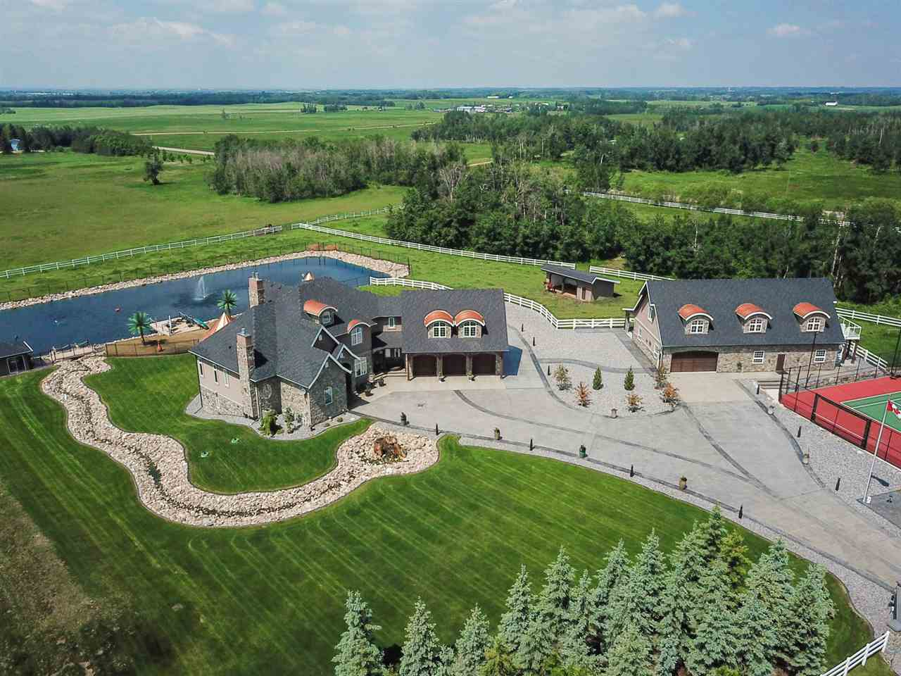 ONE OF A KIND GATED & MANICURED property MINUTES from Edmonton & Beaumont, on 4.47 acres, with an aerated SWIMMING POND, LIGHTED TENNIS COURT & SET UP FOR HORSES! Custom H & S JONES build offering over 7500 sq. ft. of GRACIOUS LIVING space in this 2 storey with a MAGNIFICENT MAIN FLOOR MASTER SUITE & a fully developed WALKOUT. COPPER DORMERS & NATURAL STONE from BC is featured on the exterior & interior of the home, SHOP & BARN. If you can DREAM it is here from the DOCK & BOAT HOUSE on the SAND BEACH overlooking the SPARKLING POND fed by a WATER FEATURE and STREAM thru the yard, to the amazing 5 STALL BARN attached to the OVERSIZED SHOP featuring a 1333 sq. ft. 2 bedroom STUDIO with balcony above! THEATRE, EXERCISE ROOM with CORK flooring, 7 fireplaces, SAFE ROOM, INDOOR PARKING for 8 VEHICLES with EPOXY FLOORS, WALNUT & WROUGHT IRON STAIRCASE, CUSTOM GLASS DOORS, ONE OF A KIND SINKS, TRAY & SOARING CUSTOM CEILINGS, BUTLERS PANTRY, EXOTIC GRANITES, TIMBERFRAME ACCENTS & PVC FENCING! IT IS SIMPLY AMAZING!