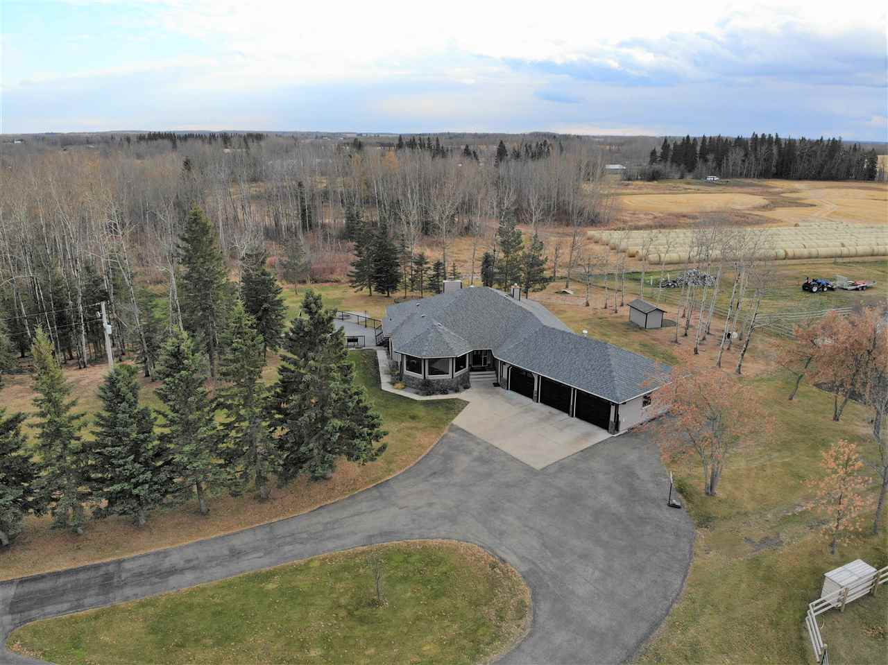 AMAZING Property & Location only 2 miles from town limits & less than a minute from Barrheads Premier 18 hole golf & country club. Modern & attractive 2035 sq ft bungalow built into the hillside w/ stylishly updated fully finished walk out bsmnt. Triple bay attached & heated oversize garage. Great open concept main living areas w/ space that can't be beat. Quality materials top to bottom including extensive new high end cork floors & more. Convenient main flr laundry & grade level entrance on both floors will make this home a reality from the raising of your family right into your twilight years ahead. Imagine the evenings & weekends watching the kids play or enjoying a peaceful country night from your expansive two tier BBQ & entertainment decks overlooking the privately sheltered back yard & fire pit areas. Unheard of 3.5 acres of post beam & chain link fenced pasture for any assortment of family animals. Too much to list & So Much to See in this fully finished package that your dreams will be made of