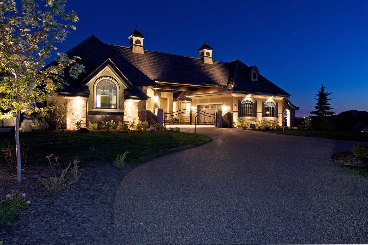 Wow! Wow! Wow! This Audie Benson Estate Homes showhome is the grandest of the grand! 7100 sq ft of luxury living on .72 acres of gorgeous river valley views in prestigious Riverstone Pointe, minutes out of St. Albert & to the Anthony Henday. The curb appeal is unsurpassed with drive through portico, natural iron stone, copper chimneys & capolas & iron security gate. Step across the threshold into an elegant foyer w/views of the Great Room, boasting 20' open vaulted cherry ceilings, an exquisite formal dining room & music room, wall-to-wall & floor to ceiling library complete with sliding ladder. The den is perfectly situated off the luxurious master suite & library. This magnificent walkout bungalow boasts awards for best kitchen & best ensuite in North America. Main floor access to the south backing upper patio, with views of double waterfalls, bridges & rose gardens. The lower level includes a gathering room, games room, theatre, old world wine cellar, fitness room w/massage area.