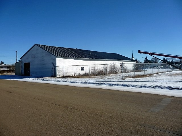 Commercial Building and Land located in Ryley, situated on a corner lot; providing excellent exposure and accessibility. Original 50x105x11 shop was built in 1939, with a 30x100x11 addition in 2000; total building square footage is 8200 sq ft. Situated on a chain link fenced compound; land base contains 35,000 sq ft or .8 of an acre. Property is currently vacant and has been previously used as a personal multi purpose shop; being sold in as is condition. Quick possession is available.