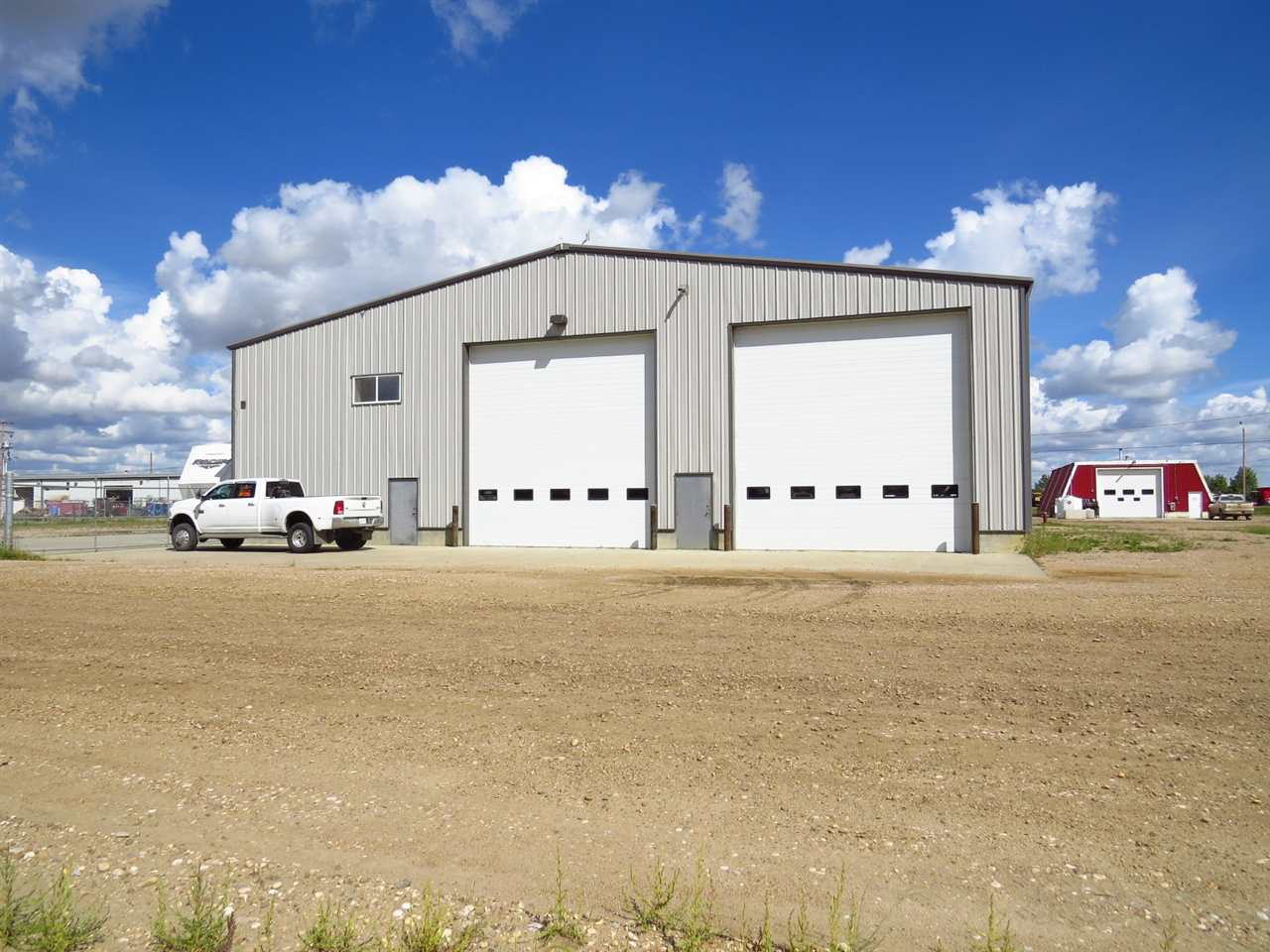 Steel Construction Shop, 8000 sqft Heated, 20ft doors! 8000 sqft Steel Heated Shop, 1600 sqft enclosed Mezzanine, Offices, Washroom, Parts Room, Work Benches and wash bay all on hi-strength reinforced concrete. 3 large doors/back and front driveway for access in and out of the shop for the equipment and all this sitting on 3 Large lots, steel security fenced and storage shed. Ideal for Heavy Equipment Company, Heavy Trucks or large Farming operation.