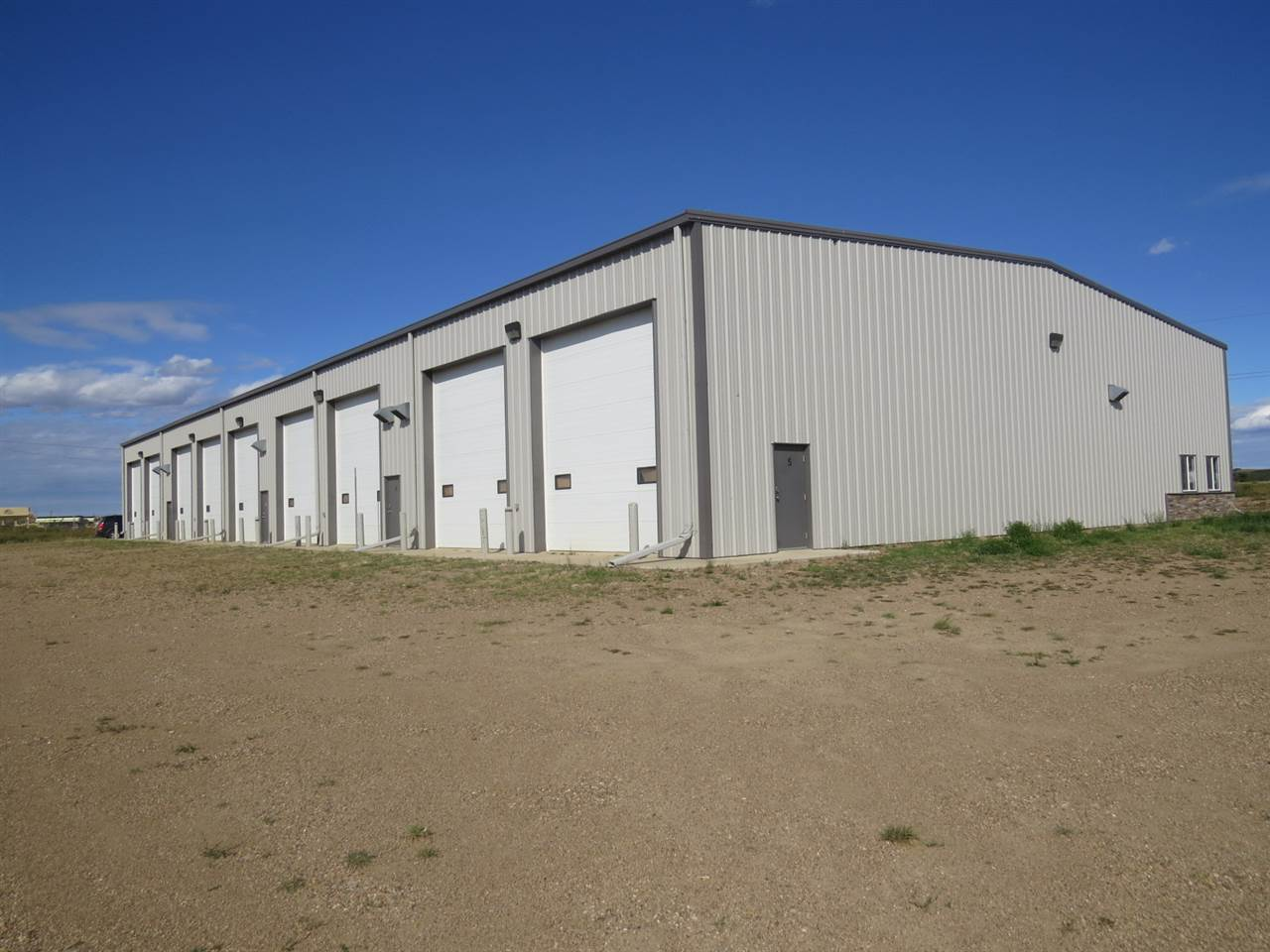 Modern Industrial Building at Hardisty on 5.10 acres! Perfect space for construction, manufacturing, and industrial operations at Hardisty built in 2014. Building has a total of 15,000sqft, 4 Double/Door Bays and 1 Single/Door Bay with separate washrooms in each. Single bay is complete with 2 bedroom Living space, Full Kitchen, Living Room and laundry service. All efficient underfloor heating design, electric doors, Sloped bay with drains and gravelled parking area on 5.10 acres. An outstanding building ready for office/storage bays, manufacturing, and business at Canada's largest oil storage facility!