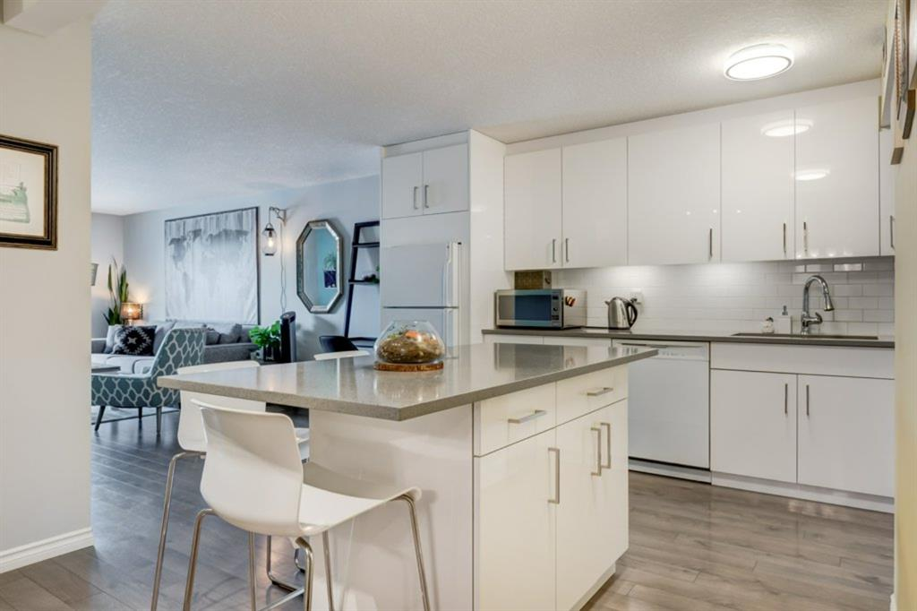 An amazing, fully renovated condominium in Killarney Manor! This urban castle is perfectly situated with easy access to downtown and so many incredible amenities nearby! Restaurants and recreation at your doorstep! The suite is beautiful, modern, with brand new laminate floors, a massive custom-built center island and kitchen cabinets with plenty of space, quartz counter tops, modern sink and taps too! The bathroom has been recently renovated with modern fixtures and finished with custom tile. THIS HOME SIMPLY GLEAMS! There is a very spacious covered balcony with glass railings installed only 2 months ago with views of downtown. Pets are allowed and two different off-leash parks are situated with a 3-minute walk. There are tennis courts and basketball courts at the nearby community center with a massive school field directly across the street. Secure covered parking is a bonus! The south facing roof top patio is fabulous and a great place to catch some rays or entertain, watch the fireworks downtown or just chill! Out your door you can walk to the LRT, Shaganappi Golf Course, Killarney Pool, so many restaurants, a local pub, specialty wine store, hot yoga, outdoor skating rink with fire pit, this home has such a great lifestyle you will absolutely love it! Check out our aerial photos, video and explore our 3D floorplan, then call us to get inside!
