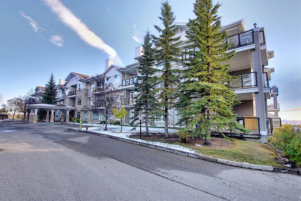 Rare Find! Welcome to this amazing corner unit with breathtaking views of the MOUNTAINS, C.O.P, and CITY views with lake access in the Arbour Lake NW community. Will accommodate a young family or mature couple. This unit features just over 1134 Sq.ft with 2 spacious bedrooms, 2  baths, den,  2 TITLED PARKING STALLS, one assigned storage locker. Bright and open concept with tons of windows letting in the natural lighting all day long. Large entertainer's dream kitchen with an abundance of cabinets and quartz counter space, island, and pantry with plenty of room for more storage, dining area,in-suite laundry..Cozy living room with gas fireplace with wall air conditioning for those hot summer days and with an SW facing covered balcony with gas BBQ hook up. Enjoy the high ceilings, in-floor heating, crown molding, and hardwood flooring. Master bedroom with builtin in cabinets with large closet space and a 3 piece ensuite. an additional 2nd bedroom features builtin in bookshelves and a builtin table with a pull-down Murphy bed for your guests plus a 4 piece main floor bathroom. Den area with a built-in desk unit for your home office. One titled secured indoor heated stall # 95 plus one outside stall close to front entrance #21 and one assigned storage locker  #106. This building has plenty of guest parking. Workshop and main floor party room with a  guest suite to rent for $45.00 per night, no age restrictions in this complex. Walking distance to schools, close to shopping, transit, very conveniently located to many more amenities. Fantastic Location!