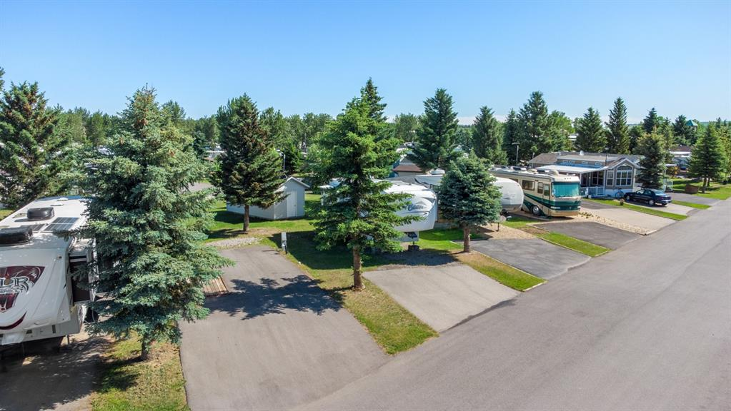 Own your own RV campsite just 15 minutes south of Calgary on the banks of the Sheep River! This premium lot backs onto common space so here you will have fewer neighbours than most lots and it is conveniently located walking distance to the clubhouse and the river. Sitting on the lot is a high end, large, 4 season 5th wheel trailer that the seller would also consider selling. The 7000 sq ft clubhouse is open from April 1 to October 31 (200 days a year) and includes a  games room, a great room for large groups or activities, a gym, a laundromat and a lounge.  In addition you will find an outdoor pool, washrooms, showers and much more. This lot is a clean slate so here you can choose exactly how you would like it all laid out. Build yourself a deck, put up a shed, do a little landscaping, and make it perfect FOR YOU!!!!! Book a private tour at your convenience.