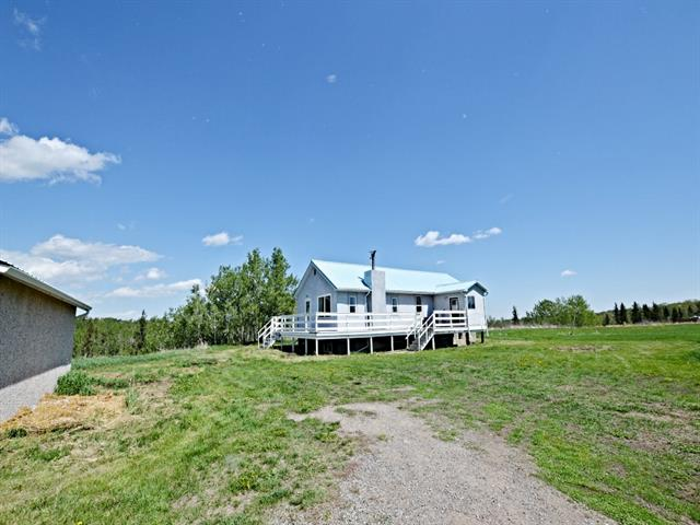 9.8 Acres overlooking the Sheep River! Spectacular MOUNTAIN,RIVER and VALLEY VIEWS! Flat Site on the outskirts of Town, zoned Urban Reserve with limitless possibilities. Bungalow was moved onto a full basement in 1988 and could use some TLC. Spacious kitchen and dining areas with wood burning fireplace in the living room. The full basement has two more bedrooms and could easily accommodate a large family room. Real Property report has been ordered. The current wells are non-producing, the owner hauls water. This location is slated for town water in the future. Future development plan is a possibility. Great holding property!