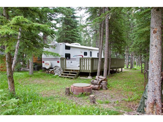 Lot 201 - Large lot along a lazy creek in a quiet part of Riverside RV Village in Sundre.  Relax on the spacious 25x10 deck amongst the spruce.  28' trailer has 13' slide, separate master bedroom, bunk beds, a roomy bathroom, and excellent kitchen/eating area.  8x8 storage shed to keep things neat and tidy.  Spend family evenings around the fire pit by the creek.  Household goods in trailer and shed are included. Riverside RV Village has seasonal water and sewer, a clubhouse with washrooms and a playground, and year-round washrooms for winter campers.  Located right in Sundre, only blocks from shops and restaurants, right along the Red Deer River.  An easy weekend getaway from the city!