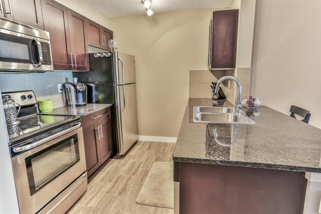 *CONDO FEES PAID FOR 6 MONTHS* Beautifully presented upgraded condo (Evolution floorplan) with 2 bed, 2 baths and a den, with gorgeous flooring throughout (no carpet in this unit!).  This great condo also benefits from a titled underground parking space and a storage unit!  The kitchen has dark cabinets, gleaming granite counters, stainless steel appliances and an eating bar.  There is space for a dining table and the living room has a door leading onto your covered patio, perfect for relaxing after a long day!  There is a spacious den which is great for a home office.  Both bedrooms are large and the master has a walk through closet and a 3 piece ensuite with oversized shower.  There is also a 4 piece family bathroom and a stacked front loading washer/dryer.  All this and in a great location close to transport links, south Calgary Health campus, playparks and walking paths.  Don't miss out!  View this UPGRADED condo today!