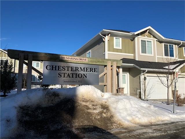 Fantastic 2 bedroom main floor condo located in desirable Chestermere Station. This main floor (just a few steps below grade), open concept, corner unit with large windows and large island is ready to move in, or alternatively to have as a fully managed investment property with management in place. Built in 2012 this condo shows very well with neutral paint colour.In Suite Laundry. Builder size 797 SF. Assigned parking with potential to rent additional stalls and low condo fees make this a great starter home or investment property. The condo is just around the corner from a shopping area with groceries, restaurants and anything else you may need as well as steps away from the lake and paths making it a perfect location. An easy drive to Calgary via 16th Ave or 17th Ave in the NE. Walking Distance to all Amenities