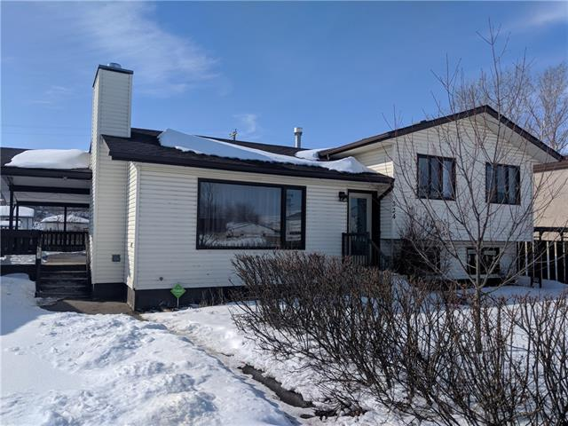 """MOTIVATED SELLER!! Come and check out this great home in the charming """"Village in the Valley""""! Three bedrooms and  two and a half bathrooms make this a great home for your family. The open concept main floor has an oak kitchen and wood-burning fireplace, along with new engineered hardwood floor! The two lower levels have carpet and more family space! The roof was recently shingled and the furnace has a clean bill of health! Large fenced yard with fruit trees and large wraparound deck. Double detached garage and an additional single detached garage gives you lots of storage and tinker space! This home will not be on the market long!"""