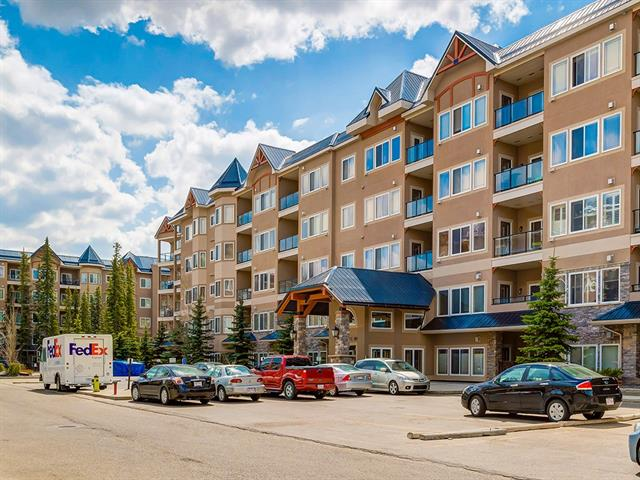"""Beautifully maintained unit in the highly coveted """"10"""" building. This condominium community is nestled in one of the most beautiful condo settings in Calgary. Featuring one of the larger floor plans, this unit faces Griffith Park environmental reserve and truly has it all... 2 parking spaces (titled TANDEM stall), 9ft ceilings, hand-scraped hardwood floors, granite counter-tops, S/S appliances, gas fireplace, huge laundry room, master bedroom w/ walk-in closet and oversized ensuite w/ jetted tub. Also included, plumbed natural gas to the balcony including the the BBQ and the TV and mounting bracket above the fireplace. Newly painted throughout. A must see if you are considering condo living!"""