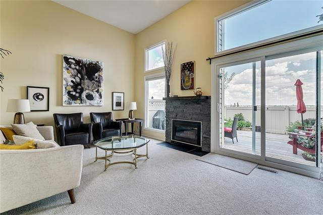 Fantastic location...ON THE RIDGE, BACKING SOUTHWEST ONTO NATURAL RESERVE-PARKLAND...180 degree views of the Bow Valley.  Likely the best position in this complex. END UNIT w/ extra west windows. Great condition w/ updates throughout. Freshly painted. The living room has vaulted 12' ceilings, a gas fireplace + double-height windows that overlook the private yard + park...stunning!  Bright + spacious eat-in kitchen. Dining room overlooks the LR. King-sized master suite w/ double closets + sparkling new 4 piece ensuite (cheater door to hall). Second bedroom w/ valley views + open TV lounge complete the upper level. New white 2 pce powder room. ATTACHED GARAGE has a new door + motor, additional storage + DIRECT ACCESS INTO THE HOME...GOOD SECURITY for single owners + great for COLD WEATHER. Fully fenced private yard w/ new deck + planters. These prime escarpment units rarely come on the market. Amazing for walks + pets...open the gate + you're in the middle of nature!