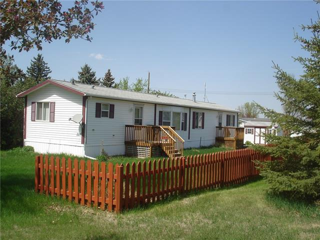Quiet, Private, well kept home in the charming Village of Carmangay. This 2008 Manufactured Home is on a Large  Treed lot in which you own. Open Concept, vaulted ceiling, 3 bedrooms, 2 bathrooms, spacious, bright and looking for new owners! Gas Fireplace in the Living Room  add to the charm of this home. Master en-suite has a large walk in shower.  Large Garden shed or workshop (12X8) in the back. Come have a look at this great property for a very affordable price.