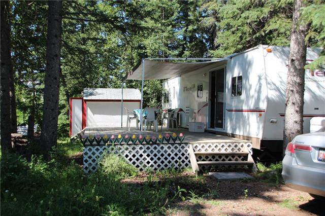 199 Riverside ? Tucked back in the deepest corner of the park, this lot is surrounded by lush natural vegetation and the beginnings of a spring feed creek. The roomy 2002 39D Fleetwood Terry Canadian Edition has a separate queen master bedroom in the front and a separate Bunkie with table in the back. Sleeps 8. It is in great shape, well maintained, with a 2012 fridge and updated carpet and upholstery. The perfect family hideway. Large glass doors lead to the southwest facing deck that can be partially covered by the trailer awning. There is a shed and a fire pit for further outdoor leisure.  Riverside is a gated recreational community on the banks of the Red Deer River in the town of Sundre, with all its close-by amenities and shopping.  It has seasonal town water and sewer, with year-round access and washroom facilities.  Come see your weekend family getaway today.
