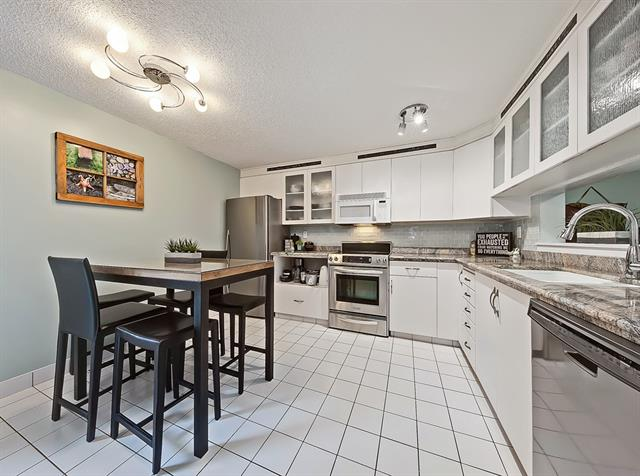Combined features make this an exceptional location in the complex. Inner unit with extra insulation, south patio, sheltered from winds. Fenced courtyards, spruce treed greenspace, no neighbours to see and great play area for kids. Renovated bright white kitchen, granite counters, newer stainless fridge, Ceran top stove, stainless dishwasher, newer lighting, marble mosaic tile floor in main bath. Sunken living room with newer warm carpet and remote corner gas fireplace. 3 beds up + 2.5 baths. Master with walk-in closet, renovated ensuite w/ large shower. All windows & patio door updated. Newer water softener, new gas BBQ hook up, upper washer & dryer & shelving in the storage room. W2 parking stalls in heated parkade plus parking for 1-2 motorcycles. Walking distance to Glenmore-Weaselhead Parks, groceries and schools (K-9). Dog and Cat friendly.