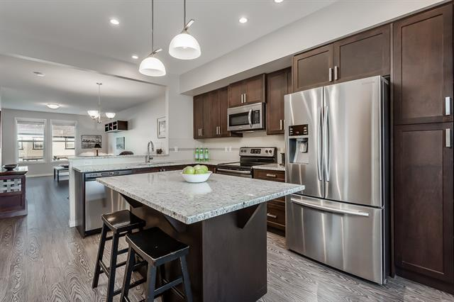Super LOW Condo Fees! You can afford NO maintenance living & a quality lifestyle in this beautiful home! Enjoy open main floor living featuring this BIG Kitchen w/ tons of cabinets, big pull out drawers, a built-in pantry, granite countertops, a huge island & SS appliances incl fridge w/ water/ice. The kitchen has easy access to the top floor deck overlooking the beautifully maintained yard. The spacious living area features a cozy fireplace. It?s the perfect space for family time or entertaining. Upstairs find 3 bedrooms and the W/D area, including a beautiful master bdrm, an ensuite w/ his/her sinks, spa sized shower & walk in closet.  The double garage has tandem parking and shelves for storage. The door from the garage also gives access to the covered 2nd deck backing right onto the greenspace. This location is one of the best in the complex with immediate access as you enter from the road. Only a short walk to the elementary school. Move in today and make this your next home!