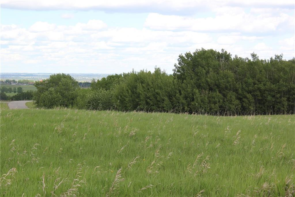 This property is a pure gem - 34.95 acre bare land parcel is nestled in the beautiful countryside of Foothills County. Prime location - just mere minutes south of Calgary's much anticipated SOUTH WEST RING ROAD. Beautiful views of the Rocky Mountains, panoramic view of Calgary including downtown, the world renowned Spruce Meadows, and countryside views from the various elevations throughout the property. From the paved road access on the West side - you will begin your walk into an open grass pasture sprawling toward the crystal clear spring fed pond that corners the expansive natural parkland wood lot of primarily aspen/poplar trees. A marked trail winds through the charming woodlot & opens up to an expansive flat north sloping pasture with the panoramic view of Calgary. Lots of possibilities - several building spots to choose from to build your walkout dream home, plenty of room for shops/barns/equestrian arenas, horse pens, grass paddocks or look to developing the property & more. A true Oasis awaits! Spring fed pond has supported trout as a private fish pond in the past. It is an acreage parcel that gives you all the experience of country life with direct city access! Experience the property by checking out our video! Call today to view!