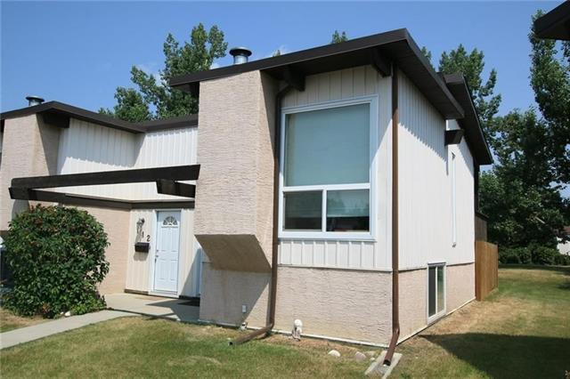 DOG OWNERS: This is perfect for you with the fenced back yard and easy pet approval. This cozy bi-level condo in desirable Oakridge is warm & inviting. The bright kitchen has newer countertops & cabinets, tiled floor & a large window that overlooks the fully fenced back yard with private deck & gate leading to the open green space. The large living room has a cozy wood-burning fireplace, & a large window that allows plenty of natural light to flood the space. The rich dark laminate flooring & vaulted, open-beam ceiling adds to the spacious, warm & comfortable feel. A 4-pce bath w/upgraded sink, tub surround & tiled floor completes the main level. Downstairs you?ll find a large master bdrm and a good sized 2nd bdrm with large windows & ample closet space. Both also have newer carpet! Large laundry & storage room completes the lower level. This condo is tucked away from the street, and is surrounded by mature trees, making it a quiet and serene place to call home. Close to transit, parks & all amenities.