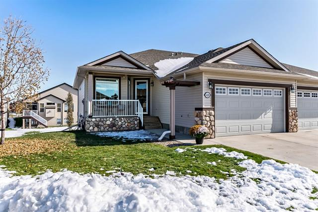 """Beautiful quality built Villa bungalow in NW High River with a large pie lot and a fully developed walk-out basement! Over 2150 sq. feet developed! Modern, contemporary plan with an open kitchen/dining and living room featuring a cozy gas fireplace. At the front entrance you are greeted on the left with an office/den and on the right side, a 2 piece bath, main floor laundry and garage access. Gleaming hardwood flows from front entrance through to kitchen/ dining area. Garden door off kitchen leads to back deck with a Phantom screen door. Downstairs includes spacious family room with a  Valor radiant heat fireplace, 60 oz. carpet, wet bar with double sink and 55""""TV with surround sound, and sectional couch to go with it. Downstairs 4 pce. bath has heated floors and a 4'x6' tiles steam shower. Hot and cold water tap in garage. Underground sprinklers. No condo fees! Lawn mowing and snow removal services has been avail. for$97.65/month."""