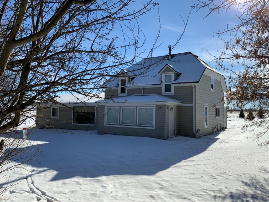 Little Acreage on the Prairie. This 1 1/2 storey character home on 5.68 acres, boasts the charm of an old house and modern technology: new windows and doors, flooring, bathrooms and kitchen, basement upgrades, new water well, new septic field, and more. The original house has 3 second storey bedrooms, up a wide curved staircase, with a main floor landing area separated from the formal dining room by garden doors, a brand new bathroom and kitchen, and a den or library and porches off both sides. The addition is a grand living room, complete with wood stove just steps down from the dining and a large master with walk in closet, ensuite and a patio walk-out facing the open prairies and sunrise. Step out into a private yard, fire pit, tire swing, and mature trees. The meandering drive is encompassed by beautiful trees, ends on a new large parking pad south of the house with a double garage.